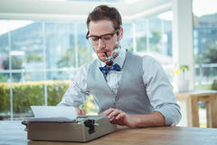 Handsome man using old fashioned typewriter Royalty Free Stock Photography