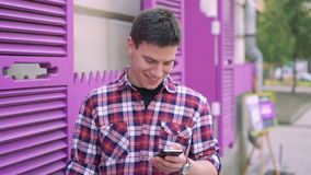 Handsome man using phone, looking aside, smiling on a background stock video footage
