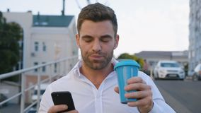 Handsome Man Using Smartphone and Drinking Delicious Coffee while Walking on Parking near Office Building. Looking stock footage