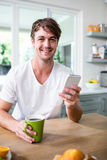 Handsome man using smartphone and holding cup Royalty Free Stock Photos