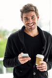 Handsome man using smartphone holding disposable cup Stock Images