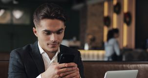 Handsome man using smartphone sitting in cafe or coworking office. Portrait of successful businessman entrepreneur stock video footage