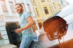 Handsome man using tablet while car being charged Stock Photo