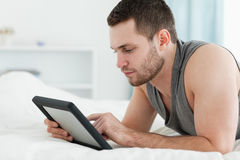 Handsome man using a tablet computer. While lying on his belly in his bedroom Royalty Free Stock Photography