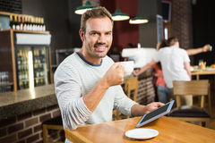 Handsome man using tablet computer and having a coffee Royalty Free Stock Photo