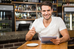 Handsome man using tablet and having coffee Royalty Free Stock Image