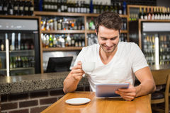 Handsome man using tablet and having coffee Stock Image