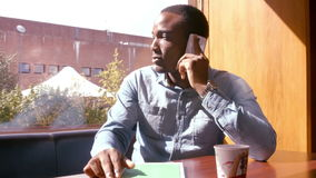 Handsome man using tablet and having a phone call. Sitting in bar stock footage