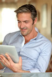 Handsome man using tablet at home Stock Photo