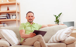 Handsome man using tablet PC at home Stock Images