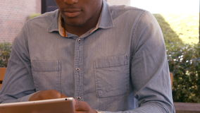 Handsome man using tablet. Sitting outdoors stock footage