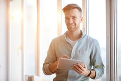 Handsome Man Using Tablet in Sunlight royalty free stock image