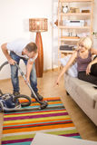Handsome man using vacuum cleaner at home Stock Image