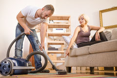 Handsome man using vacuum cleaner at home Royalty Free Stock Image