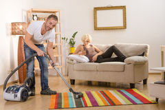 Handsome man using vacuum cleaner at home Stock Photos