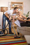 Handsome man using vacuum cleaner at home Stock Images