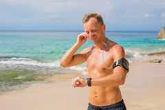 Man using wearable tech while running on the beach royalty free stock photo