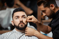 Handsome man visiting barbershop for  corection bread. Handsome and carried men visiting barbershop for  correction bread and cutting hair. Brunet hairdresser Royalty Free Stock Photos