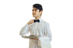 Handsome man waiter in unifrom with bowtie and silver tray in his hand looking aside Stock Image