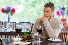 Handsome man waiting for his girlfriend at restaurant Stock Photos