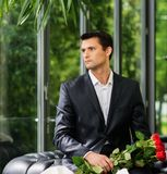 Handsome man waiting his lady in restaurant Stock Image