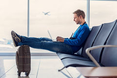 Handsome man waiting for registration. Sending quick text before take-off. Handsome young man sitting at airport and enjoying his laptop while waiting landing stock photos
