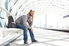 Handsome man waiting at train platform with phone Stock Images
