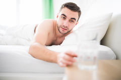 Handsome man wake up in the morning in her bed and extend to glass with water. Man wake up in the morning in her bed and extend to glass with water Royalty Free Stock Photos