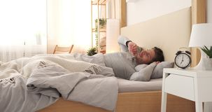 Man waking up in bed. Handsome man waking up early morning in bed stock footage