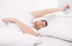 Handsome man waking up in his bedroom. Stock Images