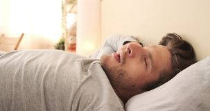 Man waking up and stretching in bed. Handsome man waking up and stretching early morning in bed stock footage