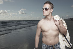 Handsome man walking on the beach Stock Photo