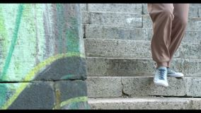 Handsome dark-haired man wearing sneakers is on stairs. Handsome Man is Walking By Gray Stairs Outdoor. Guy is Wearing Snickers Walks By Stairs in Urbanistic stock footage