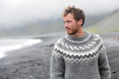 Handsome man walking on Icelandic black sand beach. Handsome man walking black sand beach on Iceland wearing Icelandic sweater. Good looking male model looking Royalty Free Stock Image
