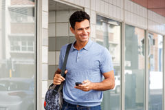 Handsome man walking with mobile phone and bag in city. Portrait of handsome man walking with mobile phone and bag in city stock images