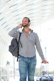 Handsome man walking with mobile phone and luggage. Portrait of handsome man walking with mobile phone and luggage Royalty Free Stock Photos