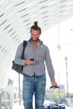 Handsome man walking with mobile phone with suitcase. Portrait of handsome man walking with mobile phone with suitcase Royalty Free Stock Images