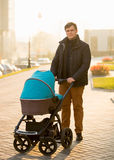 Handsome man walking with the pram on street Royalty Free Stock Image