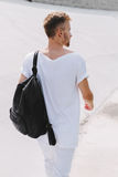 Handsome man walking in the stadium on a white background. Handsome man walking around the stadium with a backpack. Go ahead and looking away Stock Images