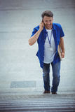 Handsome man walking on stairs while talking on mobile phone Royalty Free Stock Photos
