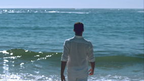 Handsome man walking towards the sea stock video footage