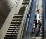 Handsome man walking up escalator with travel bags Stock Image