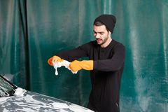 A handsome man washes a car royalty free stock photography