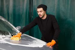 A handsome man is washing a car royalty free stock photography