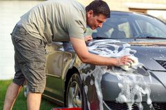 Handsome man washing car with a sponge and foam Stock Photos