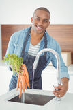 handsome man washing carrots Stock Image