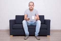Handsome man watching tv with cup of tea Royalty Free Stock Images