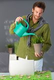 Handsome man watering plant at home Stock Photo