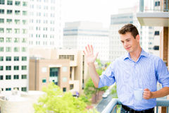 Handsome man waving from balcony and enjoying drink Stock Photo