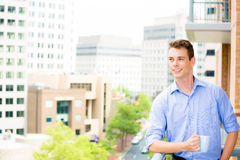 Handsome man waving from balcony and enjoying drink Stock Image